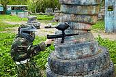 Paintball player dressed in camouflage and protective mask aims and shoots from the shelter
