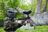 Paintball player in camouflage uniform and protective mask aims with marker into enemies from the trunk.