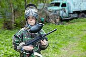 Boy in camouflage stands against the paintball area with old abandoned lorry on the background, holding paintball gun tilted on the breast