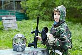 Boy in camouflage with removed protective mask holds a marker with an opened feeder and says something.