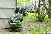 Paintball player in camouflage and protective mask hides behind shelter.