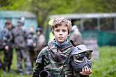 Boy in the camouflage holds a paintball gun barrel up in one hand and protective helmet in another, standing on the paintball ground with group of players on the background.