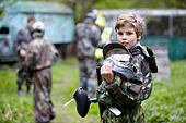 Boy in the camouflage holds a paintball gun barrel up in one han