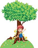 A young boy standing under a big tree