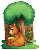 A bear sitting under a big tree