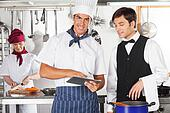 Chef With Waiter Using Digital Tablet