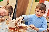 children shaping clay in pottery studio