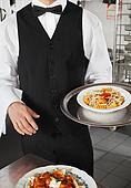 Waiter Holding Dish In Kitchen
