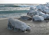 Rocks covered in ice on the sea shore