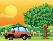 An orange vehicle near the big tree