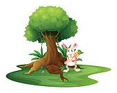 A rabbit with a carrot near the big tree