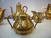 Old golden tea pot with oriental ornament