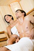 Half-naked man and lady relaxing in sauna