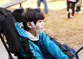 Biracial six year old disabled boy sitting in wheelchair while playing on playground. He has cerebral palsy.