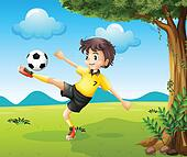 A boy playing soccer at the hill near the big tree