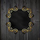 black plaque with gold patterns on a wooden background