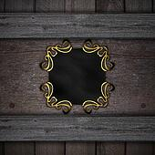 A black plaque with gold patterns on a background of wood