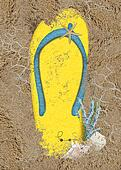 yellow flip-flop in sand