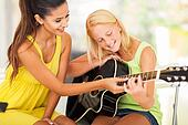 beautiful music teacher tutoring young girl to play guitar