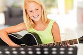 young pre teen musician playing guitar