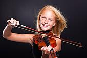 cheerful preteen girl playing violin