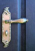The iron doorhandle on the wooden