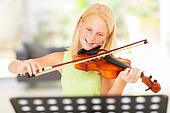 preteen girl practicing violin at home