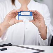 Receptionist Showing Medical Card At Counter