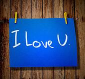 note paper and clothes peg on a wooden background with message I love you
