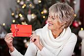 Smiling woman displaying a red Christmas voucher