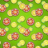 Slices of fresh citrus fruits on green polka dot background.
