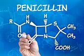 hand with pen drawing the chemical formula of Penecillin