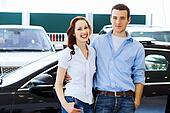 Young happy couple at car salon