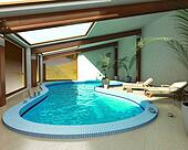 Indoor spa pool with chairs and plants.