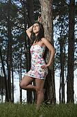 young woman in a floral tight and short dress posing in nature