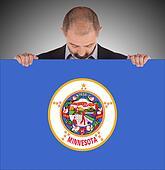 Smiling businessman holding a big card, flag of Minnesota