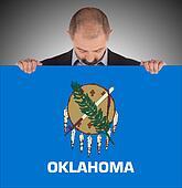 Smiling businessman holding a big card, flag of Oklahoma