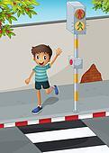 A happy boy waving his hand near the pedestrian lane