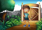 A boy inside the gated yard with a bow and arrow