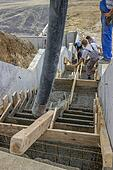 manual workers pouring concrete steps