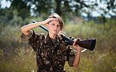 Young beautiful girl with a shotgun outdoor