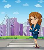 A businesswoman with a formal attire standing at the pedestrian