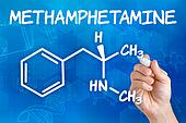 Hand with pen drawing the chemical formula of methamphetamine
