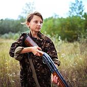 Young girl with a shotgun in an outdoor