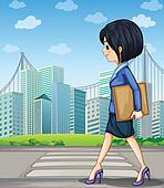 A woman walking at the street near the pedestrian lane