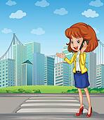 A lady with a cellphone standing at the pedestrian lane