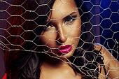 Sexy woman behind wire fence