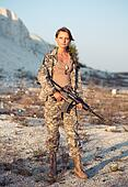 Young beautiful female soldier dressed in a camouflage with a gun in the location