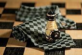 Pawn over necktie on chessboard
