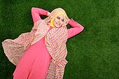 Portrait of young muslim girl wearing hijab lying on grass and looking at copy space